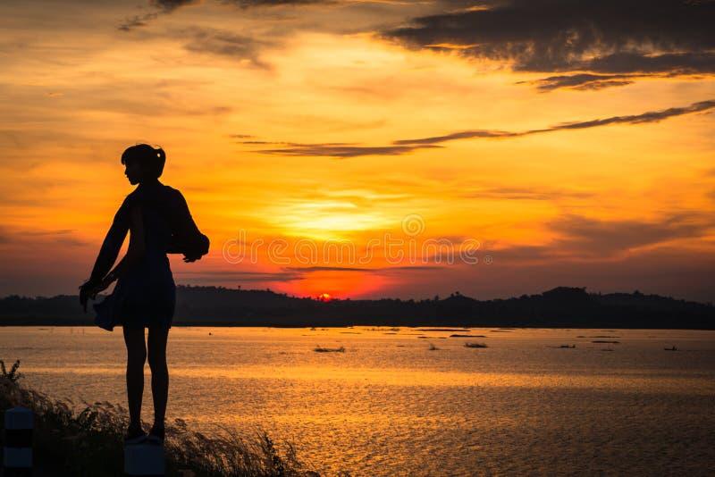 Kontur av kvinnan på sjön, soluppgångbakgrund royaltyfri fotografi