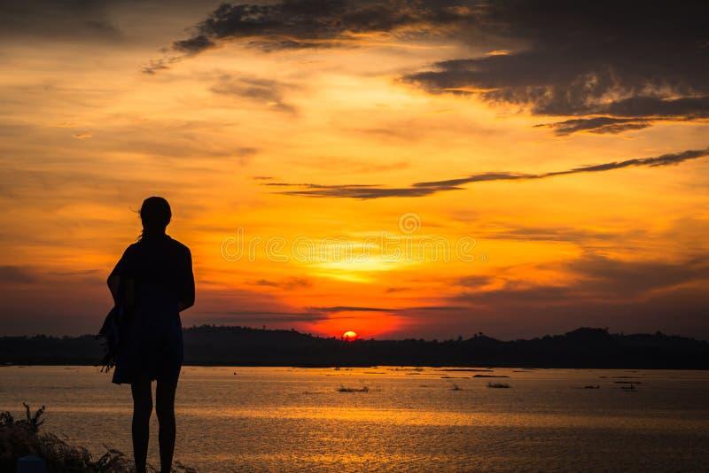 Kontur av kvinnan på sjön, soluppgångbakgrund royaltyfria foton