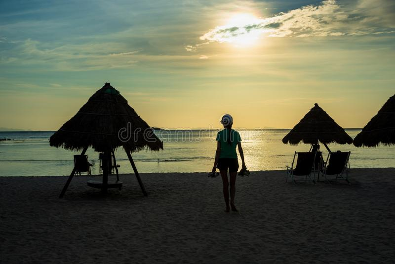 Kontur av kvinnan som bär deras skor på solnedgångstranden royaltyfri foto