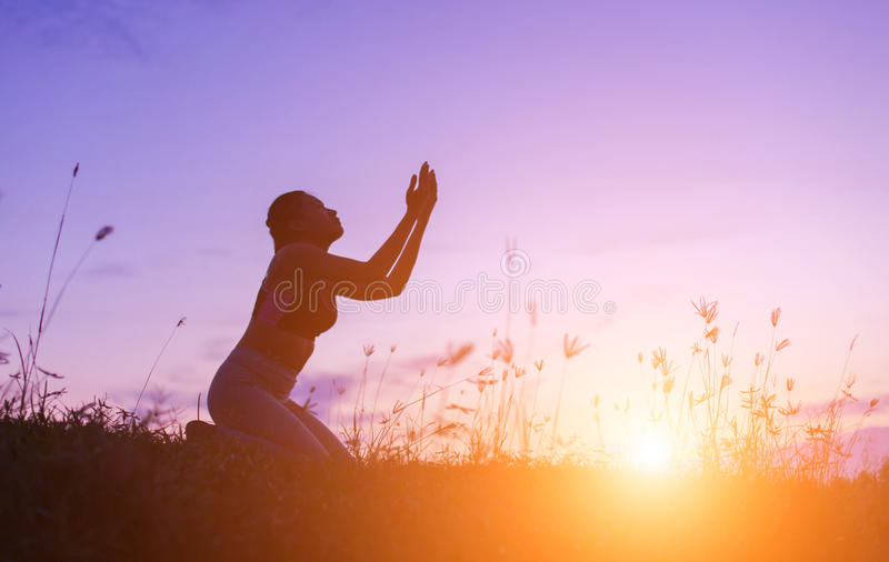 Kontur av kvinnan som ber över härlig himmelbakgrund arkivbild