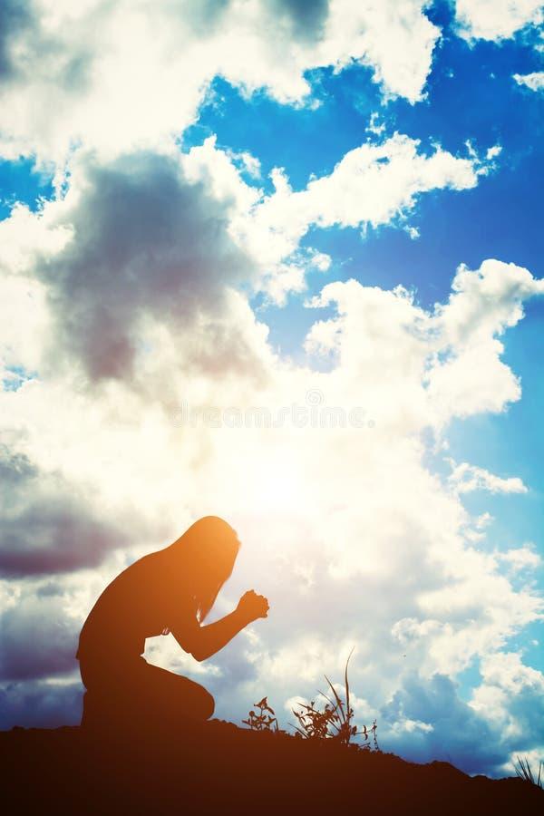 Kontur av kvinnan som ber över härlig soluppgångbakgrund arkivfoto