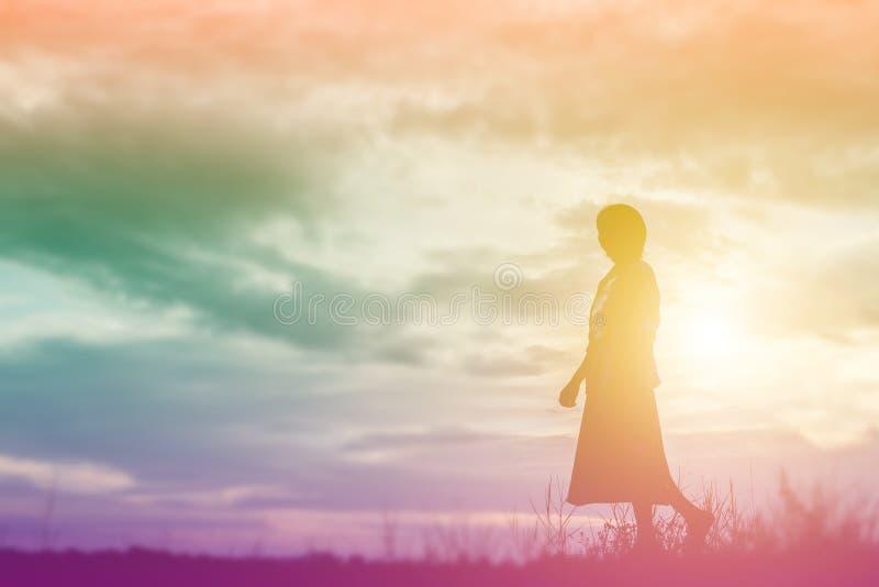 Kontur av kvinnan som ber ?ver h?rlig himmelbakgrund arkivbild
