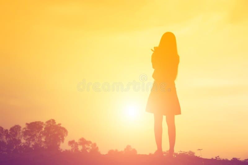 Kontur av kvinnan som ber ?ver h?rlig himmelbakgrund royaltyfria bilder