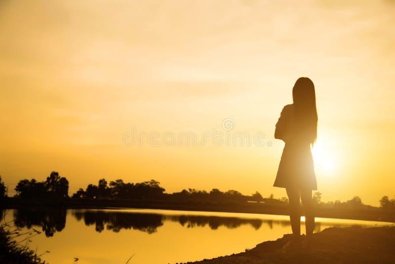 Kontur av kvinnan som ber ?ver h?rlig himmelbakgrund royaltyfri bild