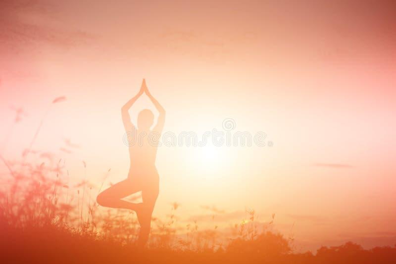 Kontur av kvinnan som ber ?ver h?rlig himmelbakgrund arkivfoton