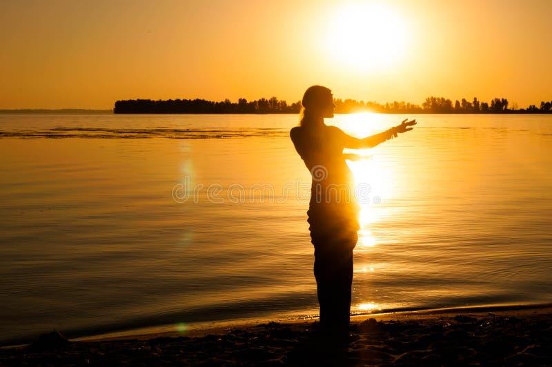 Kontur av kvinnan som dansar trible orientaliskt för tradition nära stor flodkust på gryning royaltyfri fotografi