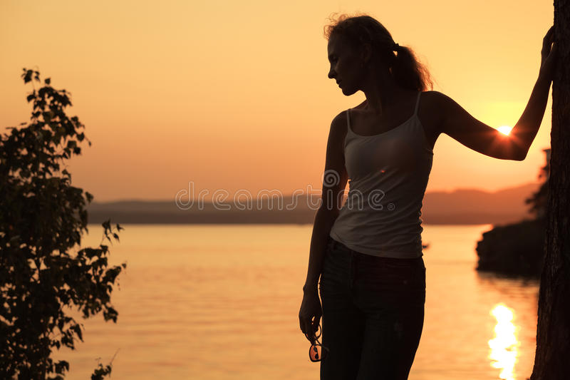 Kontur av kvinnan som som står på kusten av sjön arkivfoto