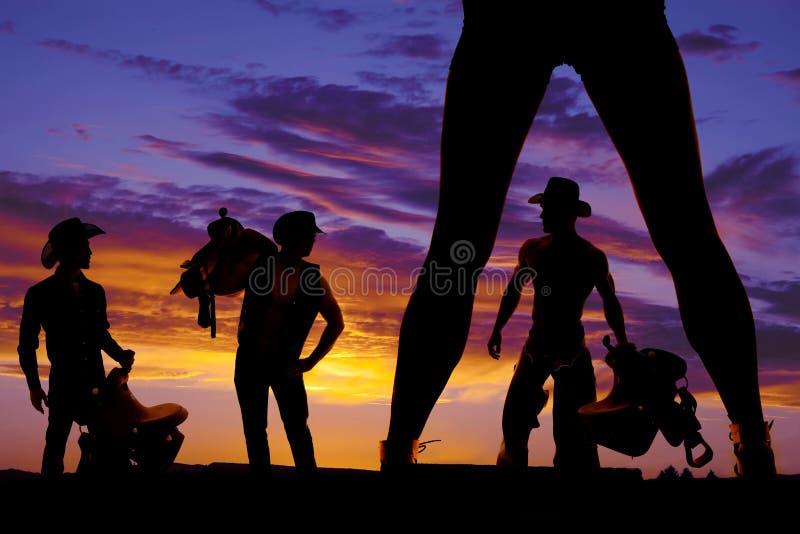 Kontur av kvinnas ben och tre cowboyer i solnedgången arkivfoto