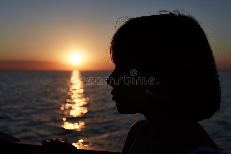 Kontur av lilla flickan som beundrar härlig havssolnedgång Hisnande naturbakgrund Gullig stående för flicka` s som kontur vid hav royaltyfri fotografi