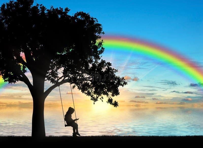 Kontur av lite flickan som läser ett boksammanträde på en gunga vid havet med en regnbåge royaltyfria foton