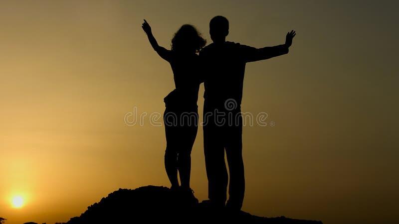 Kontur av lyckliga par som tillsammans som tycker om solnedgång ser i framtid med hopp arkivbild