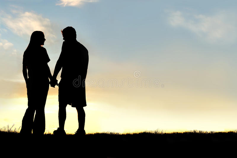 Kontur av lyckliga parinnehavhänder och samtal på solnedgången royaltyfri fotografi