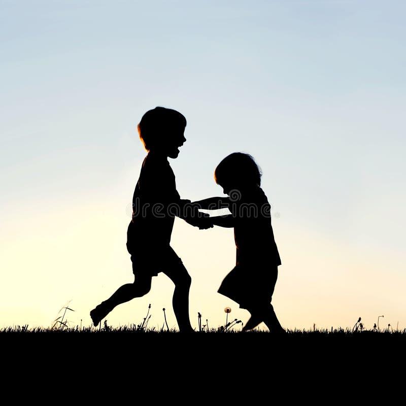 Kontur av lyckliga små barn som dansar på solnedgången royaltyfri bild