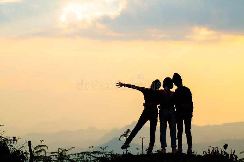 Kontur av lyckliga v?nner i bakgrund f?r tid f?r solnedg?nghimmelafton, grupp av ungdomarsom har gyckel p? sommarsemestern, ungdo royaltyfria foton