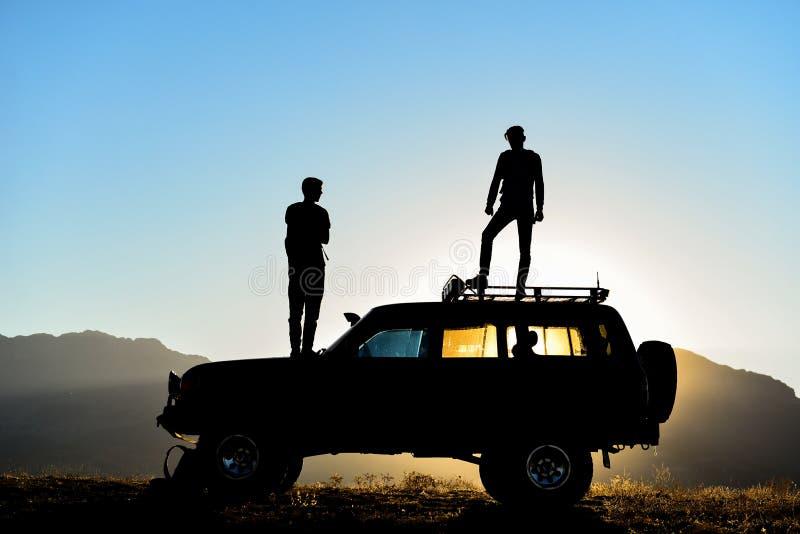 Kontur av män på SUV på solnedgången royaltyfri bild