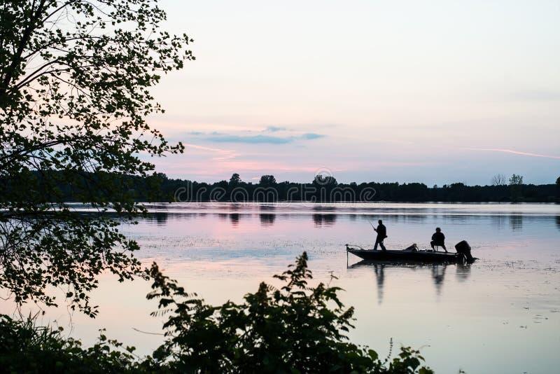 Kontur av män som fiskar från fartyget med solnedgång royaltyfri bild