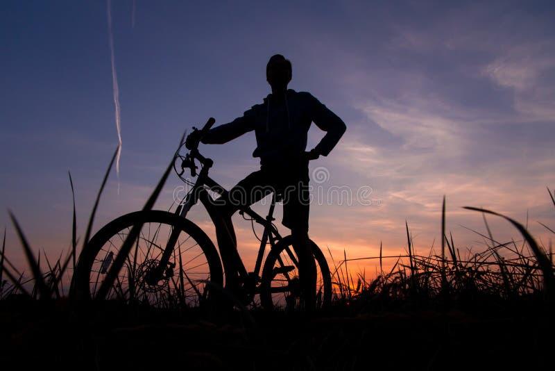 Kontur av mancyklisten på cykeln, cykel på solnedgången fotografering för bildbyråer
