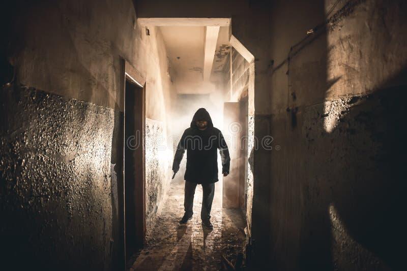 Kontur av mangalningen eller mördaren eller fasamördaren med kniven i hand i mörk kuslig och spöklik korridor Brottslig rånare fotografering för bildbyråer