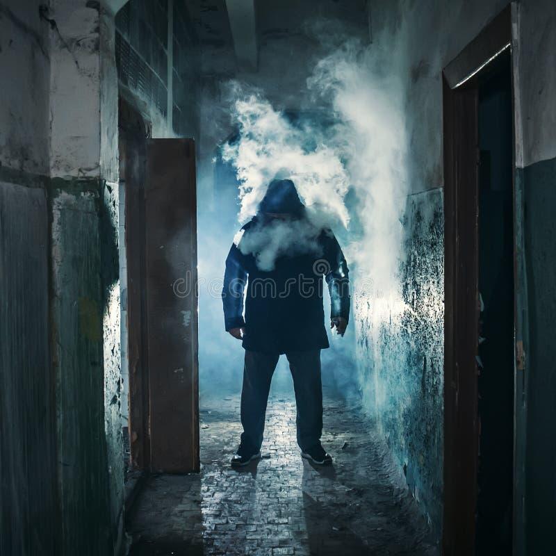 Kontur av mannen i mörk kuslig korridor i moln av vapeånga- eller dunströk, gåtafasaatmosfär arkivbilder