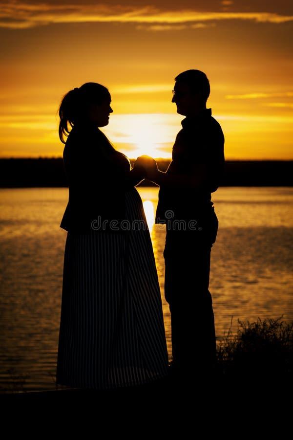 Kontur av mannen med hans gravida fru på stranden på den gula solnedgången royaltyfri fotografi