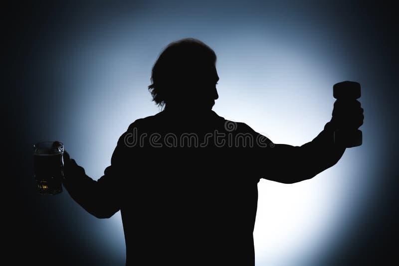 Kontur av mannen med hanteln och att råna av öl på mörk bakgrund Begrepp av valet mellan alkohol och sporten royaltyfri foto