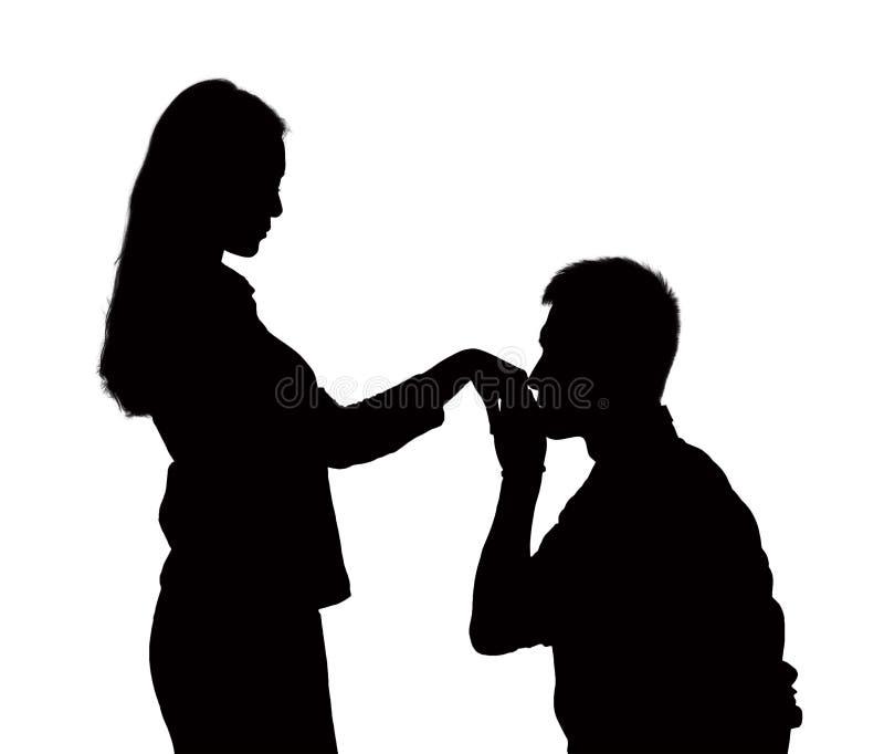 Kontur av mannen på ett knä, kyssande kvinnas hand. royaltyfri fotografi
