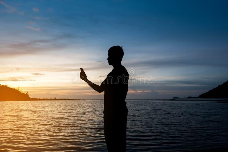 Kontur av mannen som bara står på den tropiska stranden med lugna blått arkivfoton