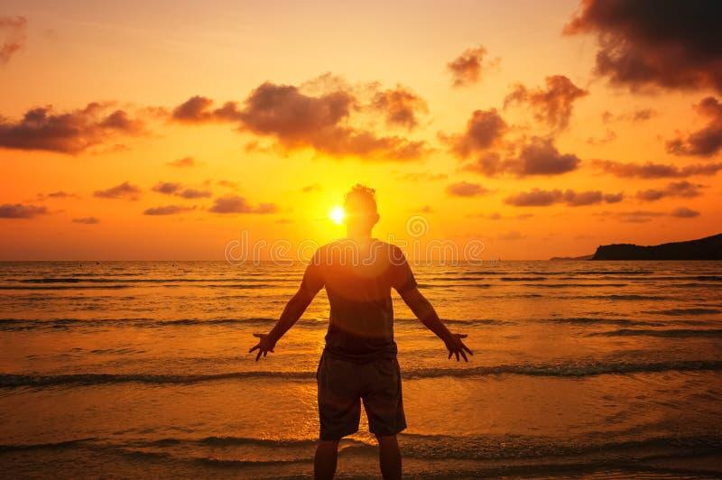Kontur av mannen som lyfter hans händer eller öppna armar med solnedgång fotografering för bildbyråer