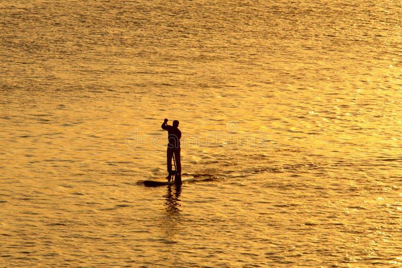 Kontur av mannen som paddleboarding royaltyfria bilder