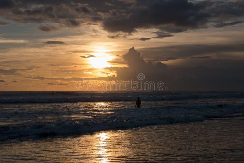 Kontur av manspring på stranden på solnedgången på den Chenggu stranden, Bali royaltyfri bild