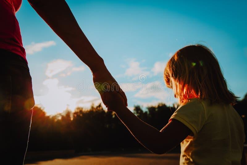 Kontur av moder- och dotterinnehavhänder på solnedgången arkivfoton
