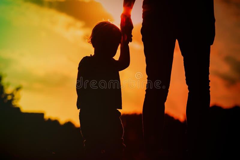 Kontur av moder- och dotterinnehavhänder på solnedgången arkivfoto