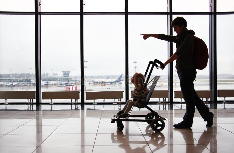Kontur av modern med hennes litet barnson i sittvagn mot fönstret på flygplatsen Mammapunkter riktningen med hennes finger royaltyfria foton