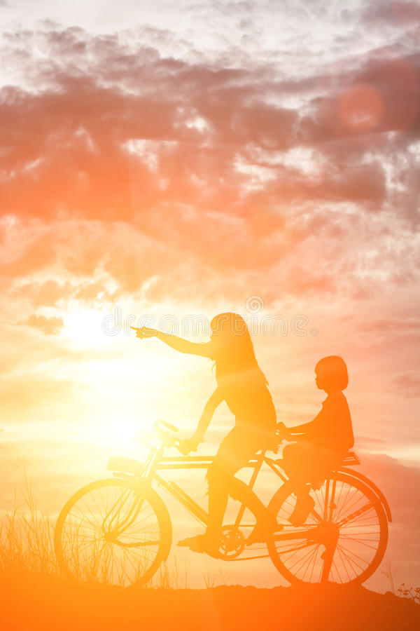 Kontur av modern och dottern som cyklar på lycklig tid för solnedgång royaltyfri bild