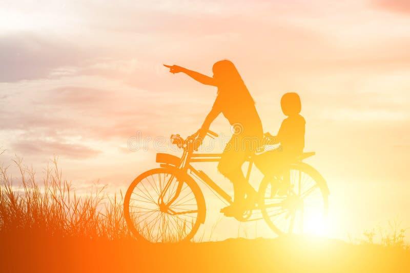 Kontur av modern och dottern som cyklar på lycklig tid för solnedgång arkivfoto