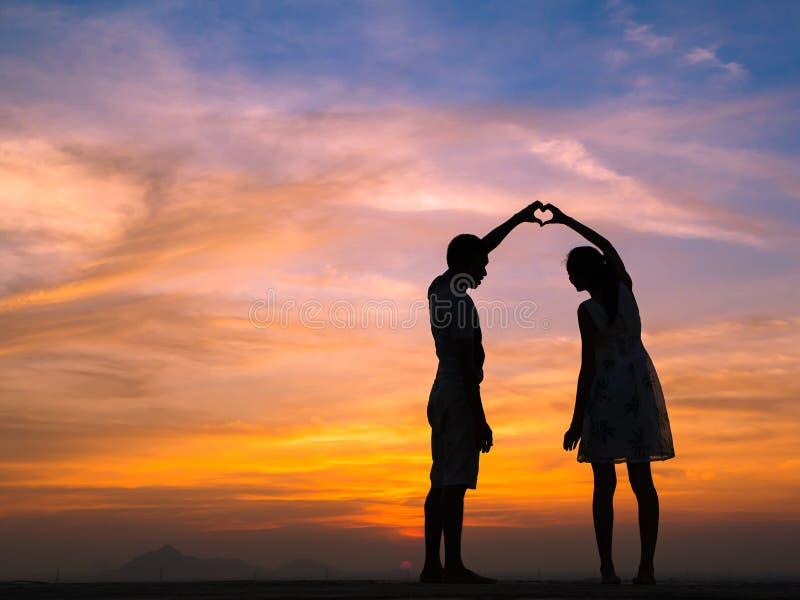 Kontur av par på solnedgången arkivbilder