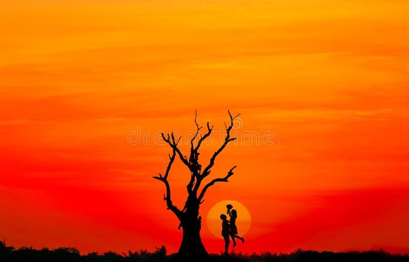Kontur av par som är förälskade med stor solnedgång och det döda trädet arkivfoton
