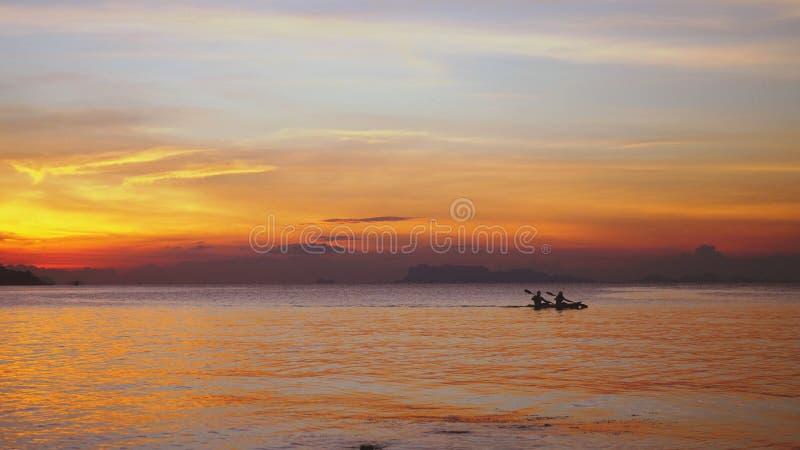 Kontur av par som kayaking på den fantastiska solnedgången royaltyfria foton