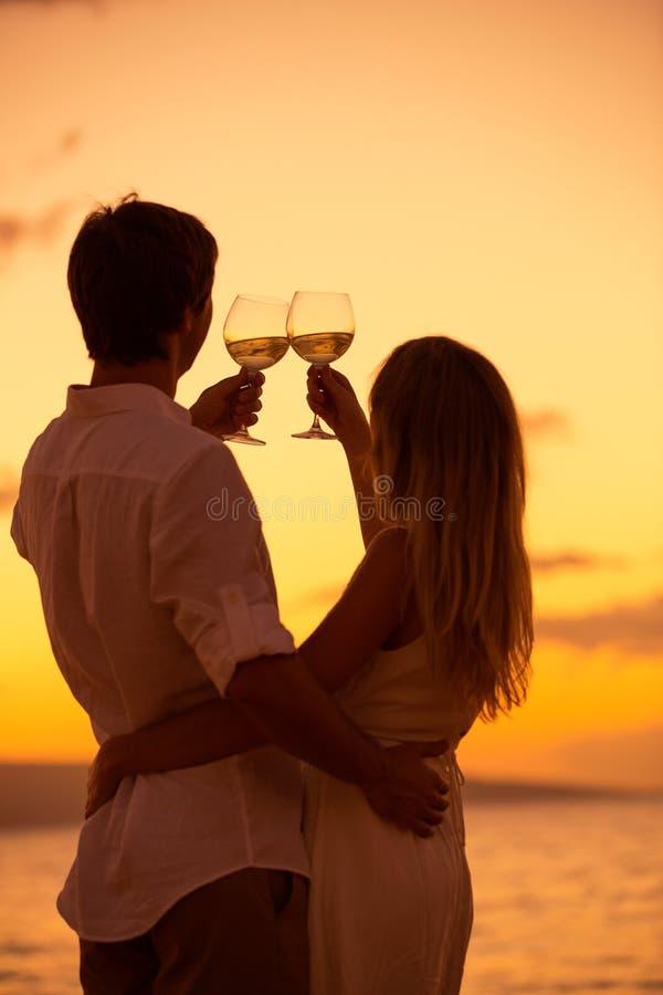 Kontur av par som tycker om exponeringsglas av champagne på den tropiska stranden arkivbilder