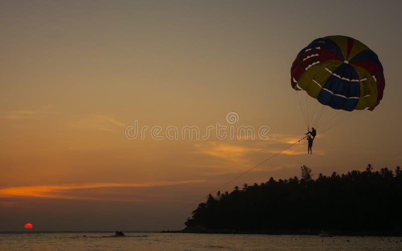 Kontur av Parasailing på den Kata stranden med solnedgångbakgrund, extrema sportar, Phuket, Thailand arkivfoton