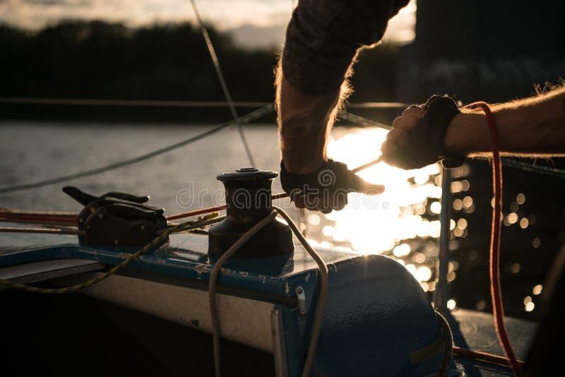 Kontur av sjömanhänder på ett vinschrep på en segelbåt på en solnedgång Skjutit med en selektiv fokus royaltyfri foto