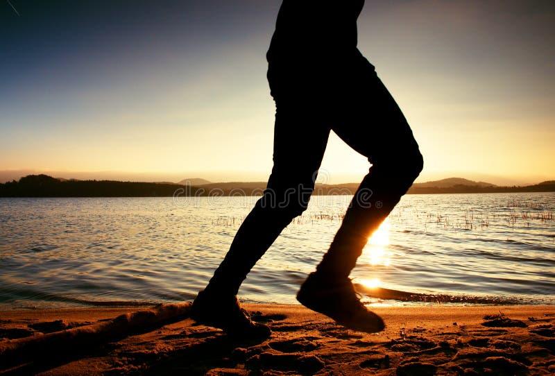 Kontur av spring och att öva för man för sport aktiv på stranden på solnedgången arkivfoton