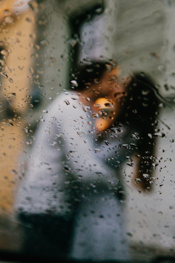 Kontur av suddiga vänner som kysser på gatan av staden Sikt från fönstret av en bil eller ett kafé royaltyfri foto