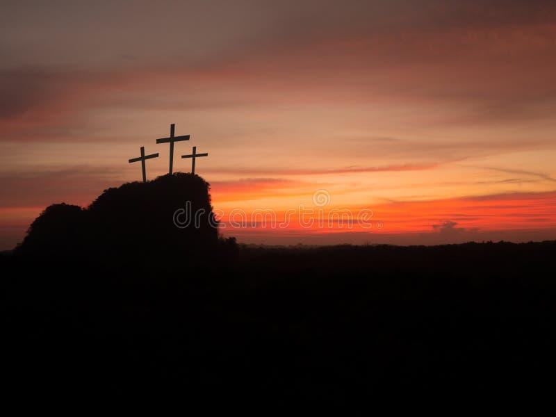 Kontur av tre kors på kullen på solnedgången Religionkorsfästelse av Jesus Christ royaltyfri foto