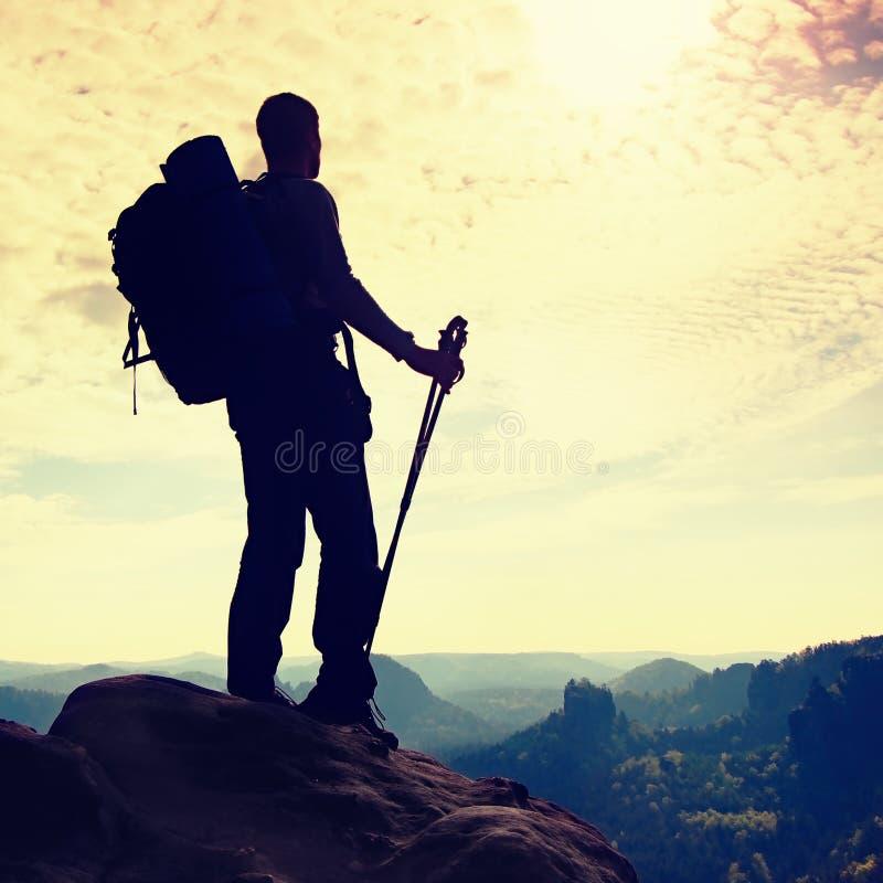Kontur av turisten med poler i hand Fotvandrare med den stora ryggsäckställningen på stenig siktspunkt ovanför den dimmiga dalen  arkivbilder