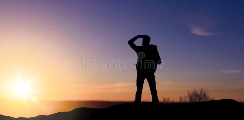 Kontur av turisten som långt borta ser över solnedgång arkivbild