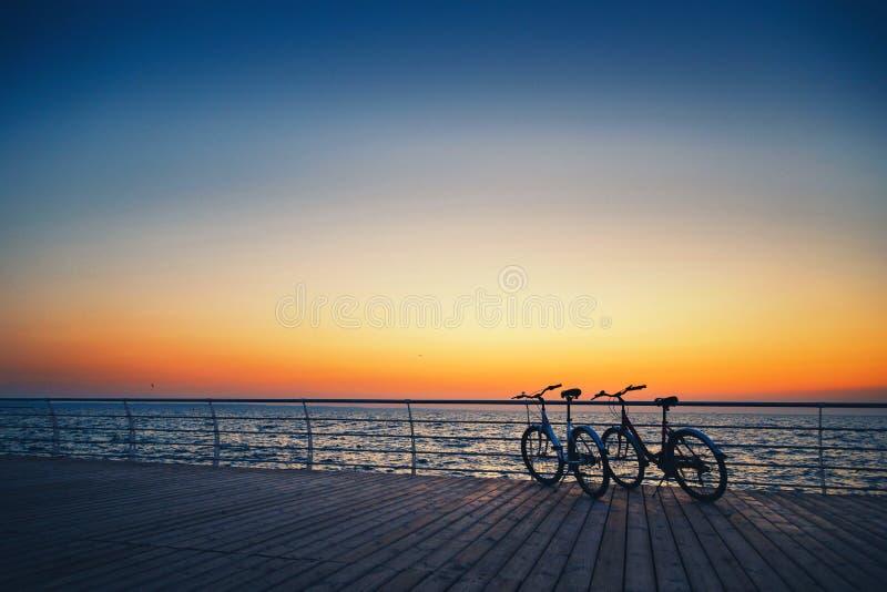 Kontur av två cyklar på stranden på soluppgånghimmel på trädäcksommartid, ritt längs kustsommarstranden på gulingblått royaltyfri foto