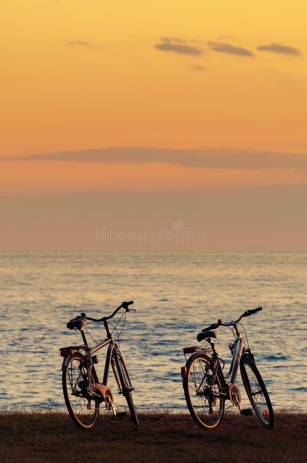 Kontur av två cyklar vid havet efter solnedgång arkivfoton