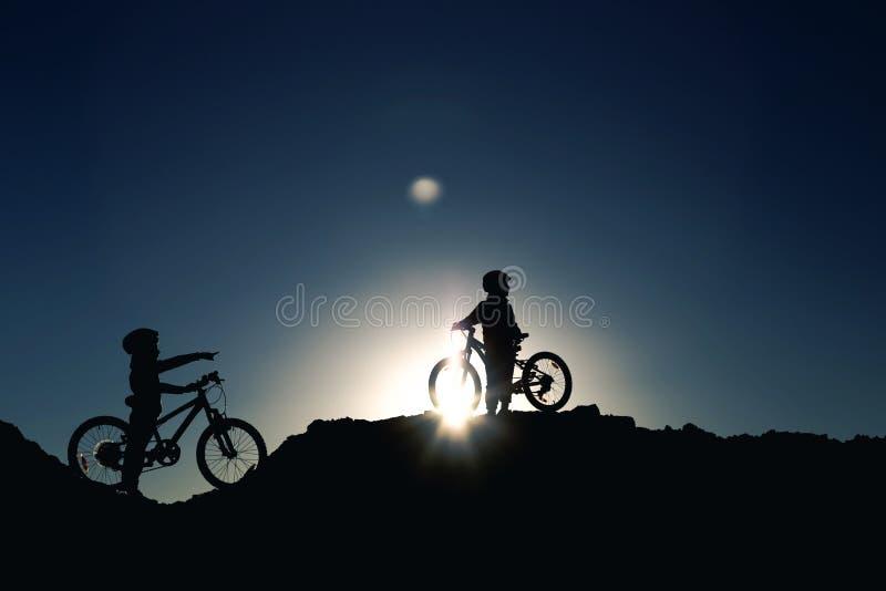Kontur av två små flickor med cyklar på solnedgången arkivbilder