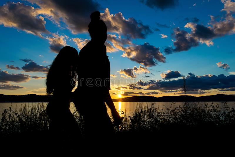 Kontur av två unga kvinnor, framme av en dramatisk och härlig solnedgång av Hudson River, Upstate New York, NY royaltyfri bild